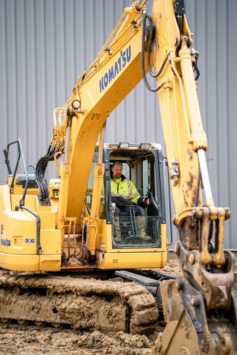 Dedicated Berg Construction Team Member Running a Komatsu Excavator at a Muddy Work Site