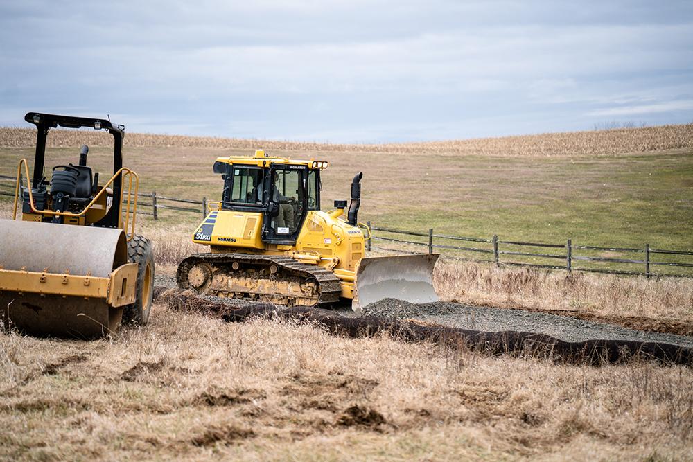 Komatsu Bulldozer Pushing Gravel Along a Path Next to an Asphalt Roller