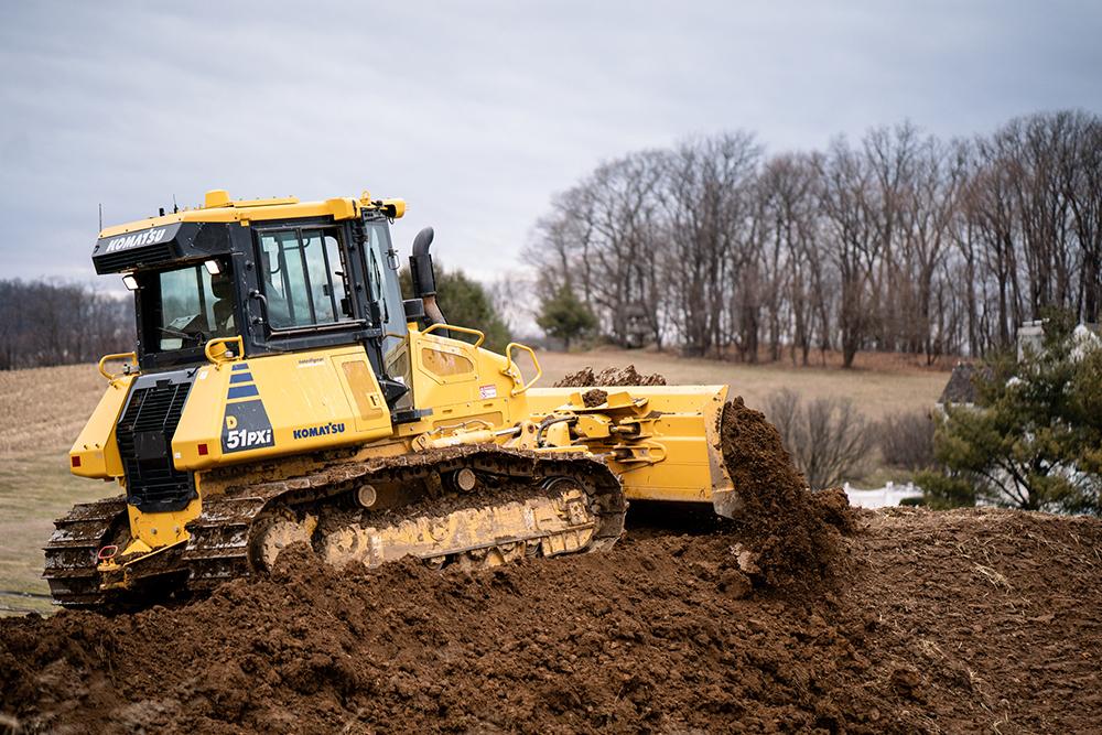 Komatsu Bulldozer Pushing Dirt and Mulch next to a Grass Field