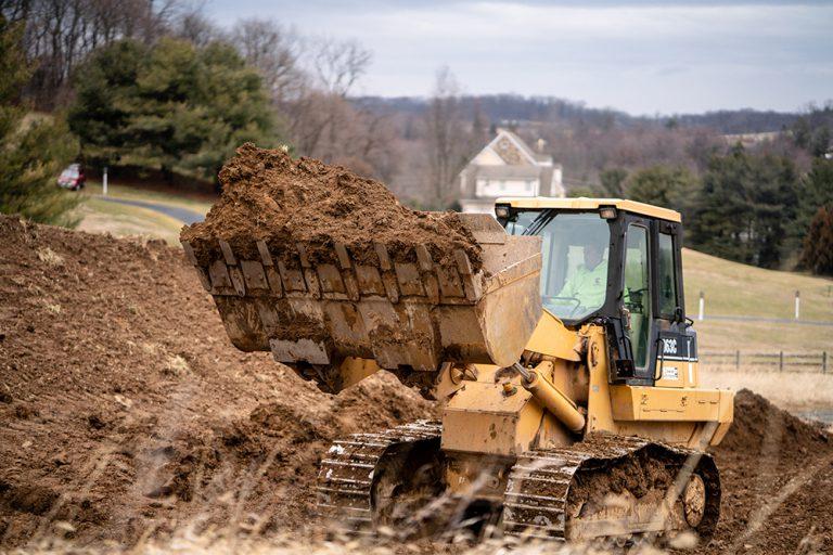 Komatsu Bulldozer Lifting Up a Large Scoop of Dirt Near a House