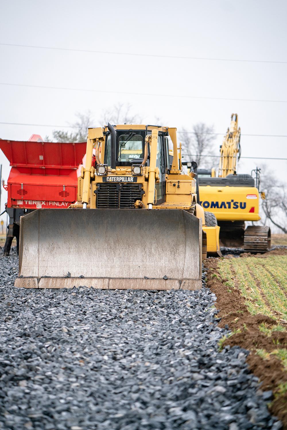 Caterpillar Bulldozer, Komatsu Excavator and Dump Truck Parked on a Gravel Path