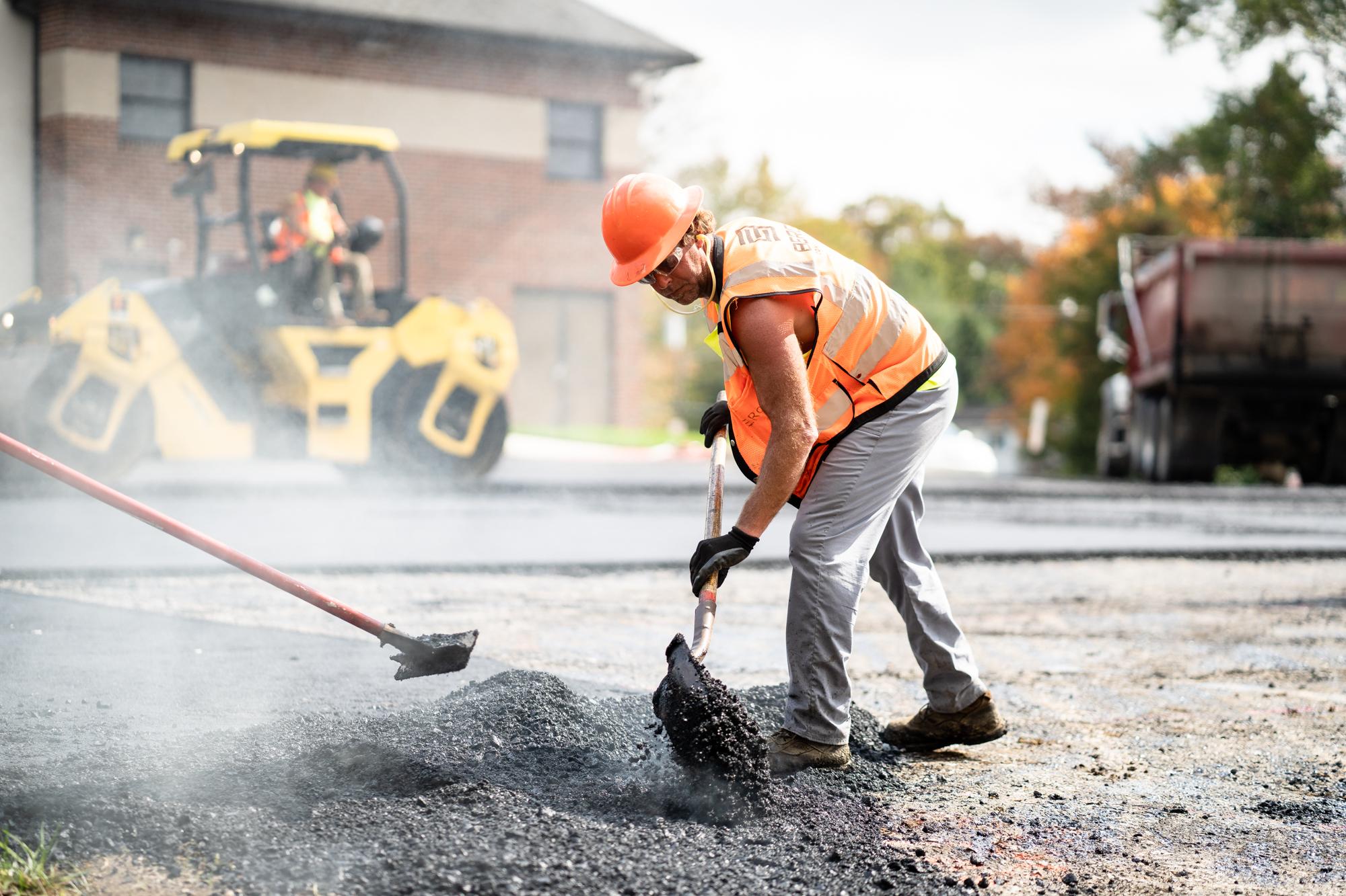 Berg Team Member Wearing an Orange Vest and Hard Hat Shoveling Asphalt at a Work Site