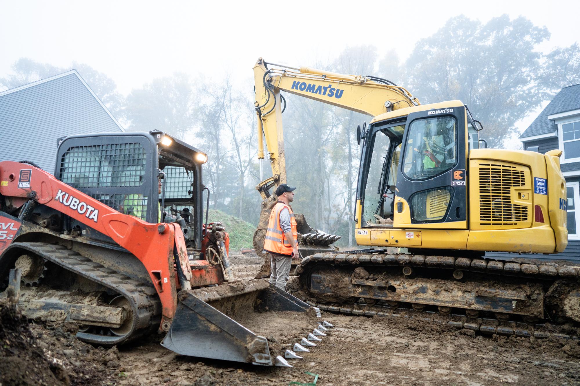 Berg Team Member Standing Between a Komatsu Excavator and Small Kubota Bulldozer at a Residential Work Site