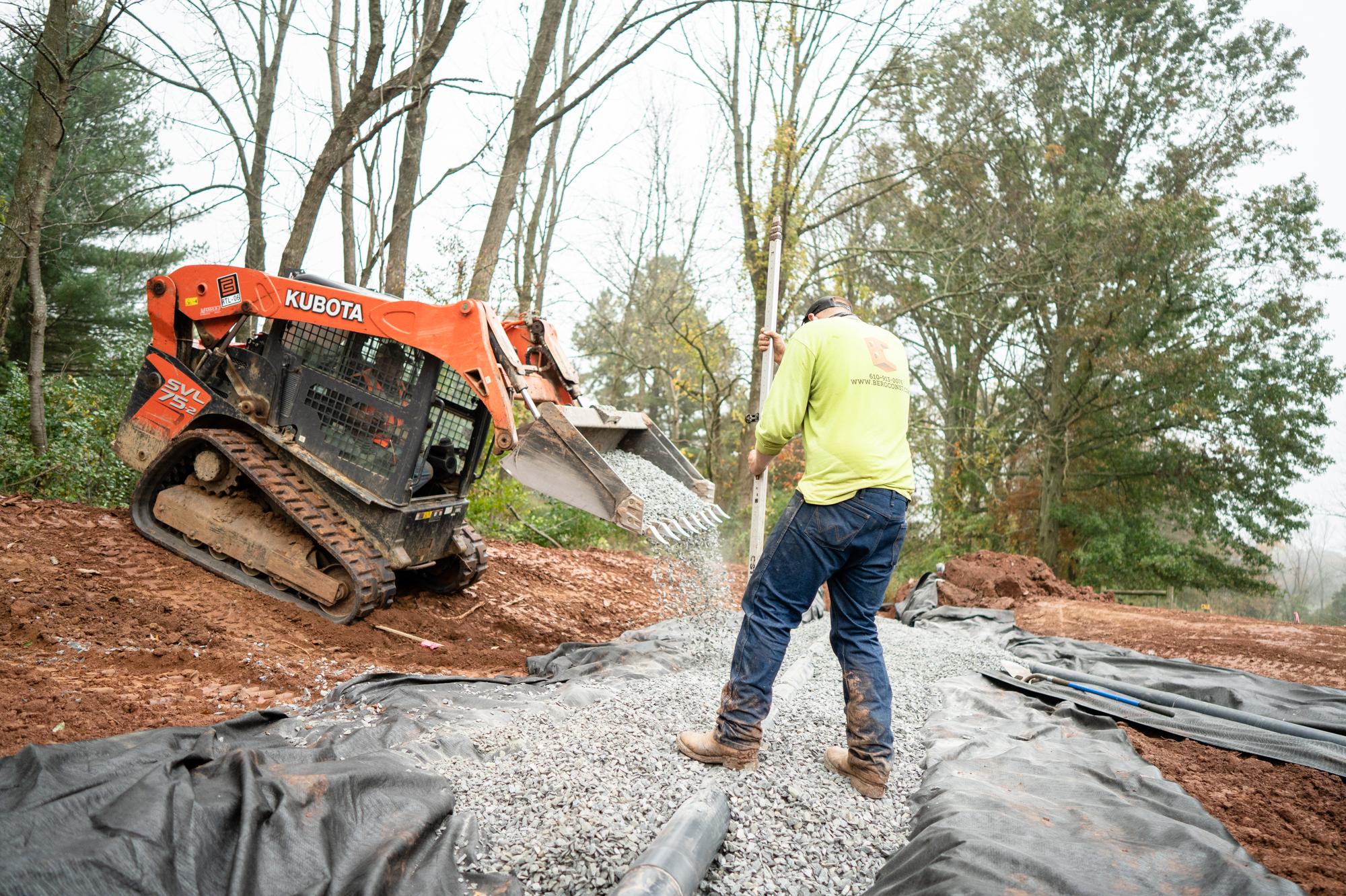Small Kubota Bulldozer Dumping Gravel Over a Pipe with a Berg Team Member Supervising