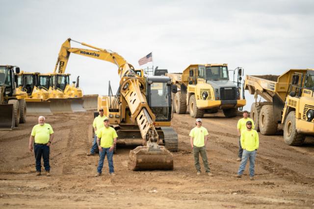 Six Members of the Berg Team Standing in From of Komatsu Bulldozers, Excavators and Dump Trucks