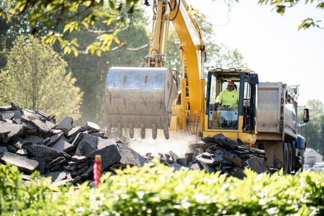 Excavator Preparing to Scoop Up Broken Pieces of Asphalt from a Pile