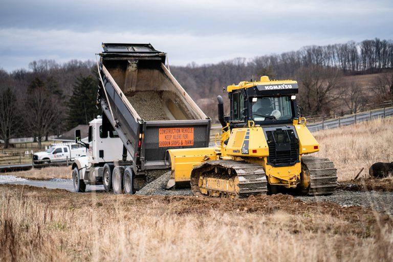 Berg Construction Dump Truck Dumping Gravel into a Komatsu Bulldozer in a Grassy Field